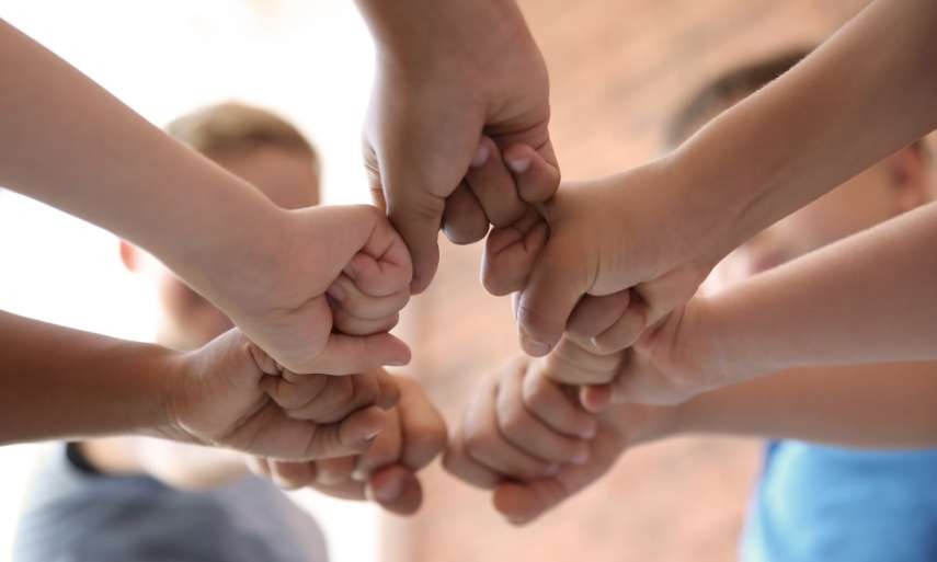 Hands joined signifying team unity.